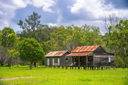 Disused wooden homestead surrounded by grazing field and dramatic stormy sky in Kroombit Tops National Park, Queensland