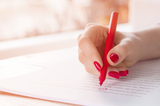 Editor or teacher hand with red pen proofreading errors in a manuscript essay