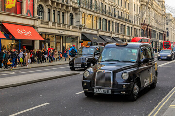 London, United Kingdom - January 13, 2018: Luxury stores on Regent street with people passing by, double decker red busses and black cabs lined up