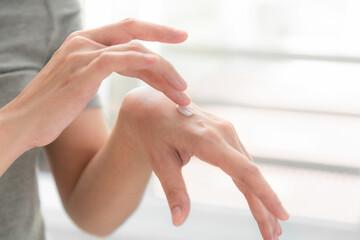 Closeup of hands applying moisturizer. Beauty woman holding care cream of skin cream.