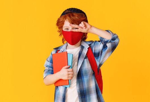 Schoolboy in mask gesturing V sign.
