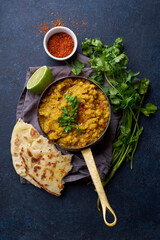 Indian red lentil curry soup dal with rice naan. Vegan indian dish on concrete background