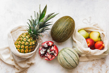 Fresh seasonal fruits (pineapple, green apples, pomegranate, peaches and melon) in eco friendly and reusable shopping mesh bags. Healthy vegan food. Zero waste. Top view, blank space