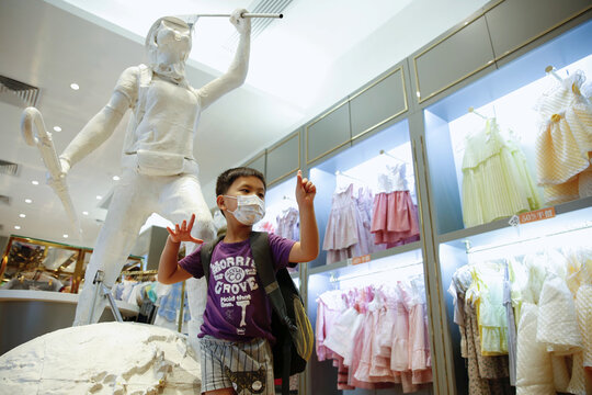 """A child poses next to the two-meter-tall """"Lady Liberty"""", a symbolic statue placed by pro-democracy protesters at a Chickeeduck branch in Hong Kong"""