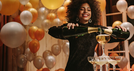 Woman filling champagne into pyramid of glasses