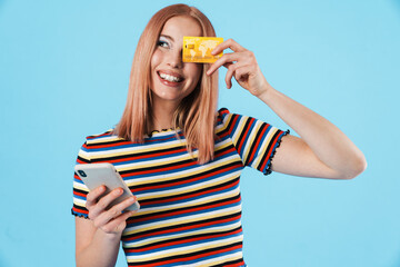 Image of laughing woman using cellphone and holding credit card