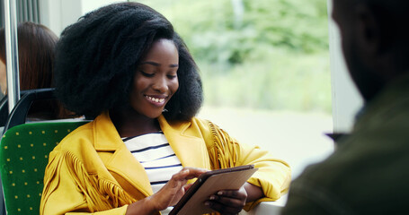Portrait of smiling african american girl with an afro hairstyle  using tablet in public transport.