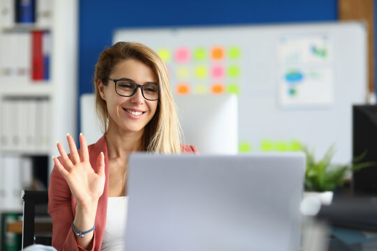 Portrait of smiling lovely lady waving hello talking on video call. Successful young woman sitting in pink jacket. Blonde happy worker. Business conference via laptop. Job concept