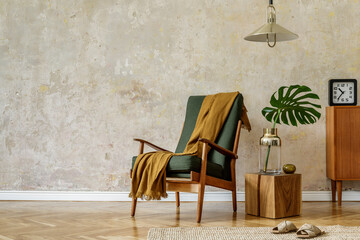 Modern retro composition of living room interior with design armchair, cube, tropical leaf, plaid, carpet, decoration and elegant presonal accessories in wabi sabi concept.