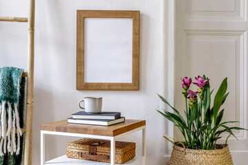 Trendy composition of home garden interior with mock up poster frame, wooden coffe table, curcuma plants, decoration, plaid, book, personal accessories in stylish home decor.