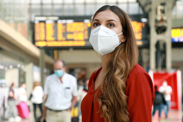 Traveler woman wearing KN95 FFP2 face mask at the airport. Young caucasian woman with behind timetables of departures arrivals waiting worried information for her flight. Wall mural