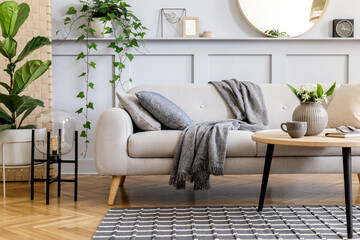 Scandinavian concept of living room interior with design sofa, coffee table, plant in pot, flowers, carpet, plaid, pillow, shelf, decoration and personal accessories in modern home staging.