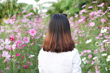travel relax vacation concept,Back view of Young happy traveler asian woman in pink flower field