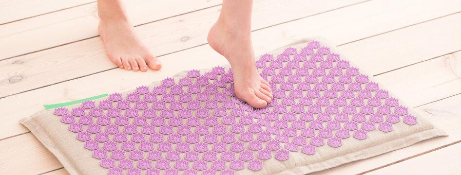 Female feet on acupressure mat. Alternative medicine and home-massage concept. Banner.