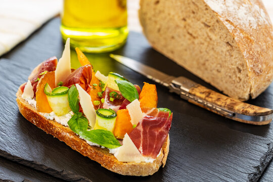 Open faced sandwich with iberico ham, parmesan cheese, goat cheese, zucchini, pumpkin, basil and chives on sourdough bread. Displayed on slates, aside olive oil, knife and bread.