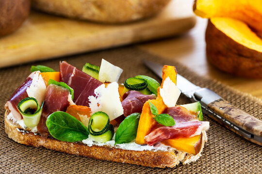 Open faced sandwich with iberico ham, parmesan cheese, goat cheese, zucchini, pumpkin, basil and chives on sourdough bread. On a natural string textile, aside sourdough bread loaf and pumpkin pieces.