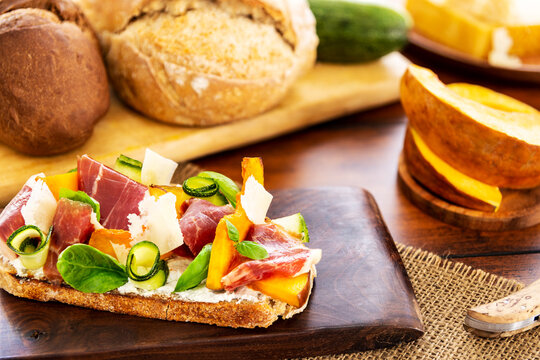 Open faced sandwich with iberico ham, parmesan and goat cheese, zucchini, pumpkin, basil and chives on sourdough bread. On a chopping board and wood, aside sourdough bread, and pumpkin pieces.