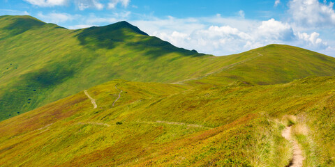 Wall Mural - trail uphill through mountain range. grass on the hills and slopes. summer landscape on a sunny day.