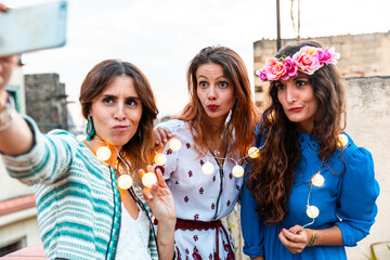 Happy women taking a selfie together at rooftop party - Three beautiful girls wearing colorful clothes and smiling at camera while holding lights - Lifestyle and friendship in Barcelona