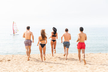 Friends having fun on the beach in Barcelona - Multiracial group of best friends enjoying summer time together running to take a swim - Happiness and friendship during a travel in Spain