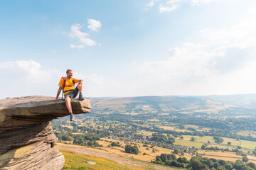 Man sitting on a rock cliff enjoying the view - Young man with backpack and hiking clothes on the cliffs over Hope Valley in the Peak District park, UK - Travel, nature and wanderlust concepts