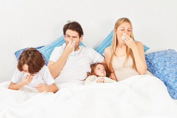 Family with two children in bed has flu