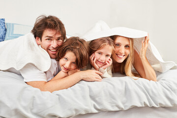 Family with two children under a coverlet