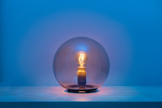 Modern turned on luminaire with light bulb inside thin transparent glass sphere in middle of shelf in blue room at dusk