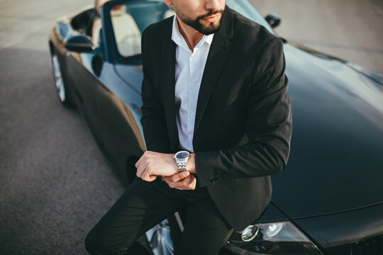 Crop attractive businessman with convertible car