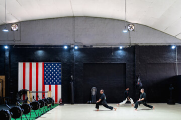 Side view of male kajukenbo practitioners performing lunges exercise during workout in spacious martial arts club with American flag