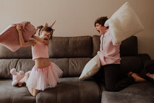 Side view of barefoot teen boy hitting sister in unicorn costume with pillow while playing on sofa together