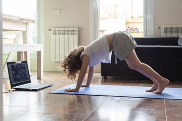 Side view of little girl doing Downward Facing Dog asana while practicing yoga in front of laptop in living room at home