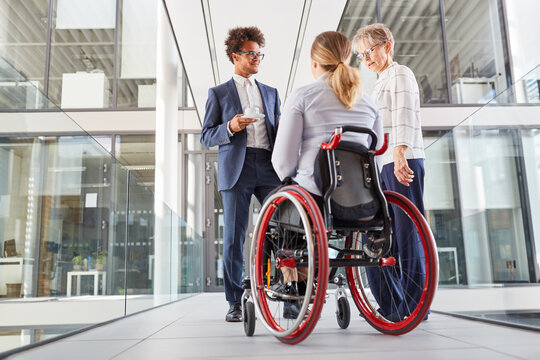 Businesswoman in a wheelchair talking to colleagues