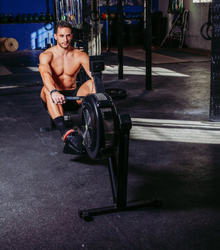 Strong sportsman using training machine in gym while pumping muscles during workout