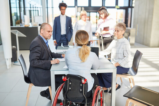 Business people with colleague in wheelchair in meeting