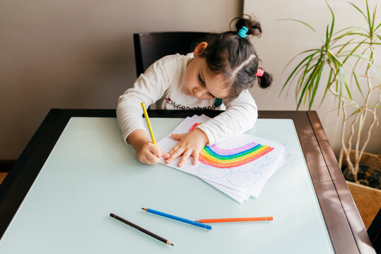 From above girl in casual clothes sitting on chair at wooden table and drawing colorful rainbow with pencil on paper