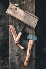 Top view of axe and knife placed on wooden rustic surface in the countryside of Finland