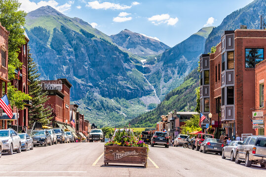Telluride, USA - August 14, 2019: Small town village in Colorado with sign for city and flowers by historic architecture on main street mountain view