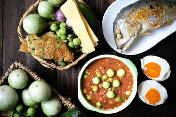 Obraz Shrimp Paste Chilli Sauce with Fried Mackerel and vegetable, (nam prik ka pi) on wood table, top view - fototapety do salonu