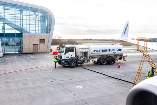 Lviv, Ukraine - January 22, 2020: Exterior of low-cost airport building in Lvov with people workers fueling Ryanair airplane in Ukrainian city