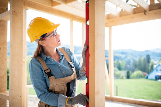 Woman worker at building site of wood frame house using level tools