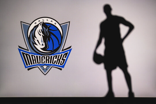 NEW YORK, USA, JUN 18, 2020: Dallas Mavericks logo of professional basketball club in american league. Silhouette of basket player in foreground. Sport concept photo, edit space.