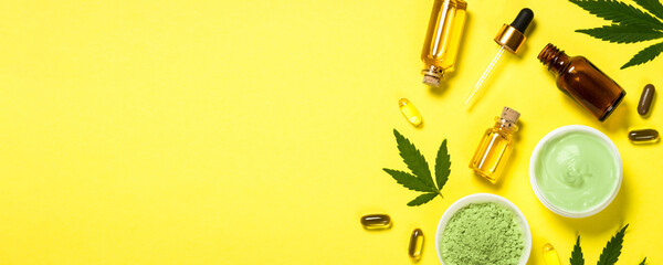 Cannabis oil and green leaves at yellow table.