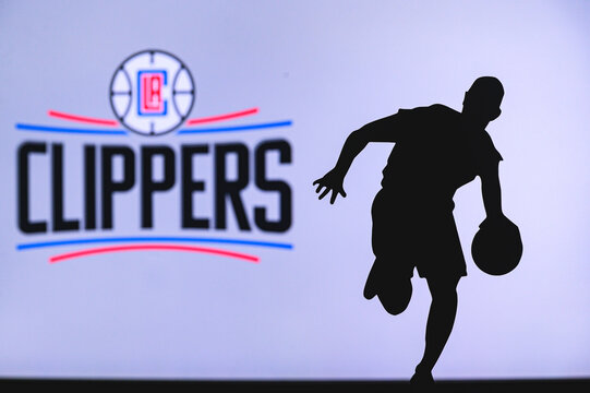 NEW YORK, USA, JUN 18, 2020: Los Angeles Clippers basketball club logo and silhouette of young basketball player. Sport wallpaper, white edit space in background.