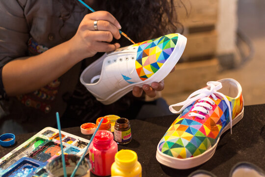 A female designer painting a shoe.