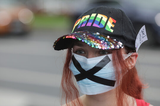 Girl wearing a PRIDE cap and a face mask bearing a black X attends an LGBT event outside the president's office