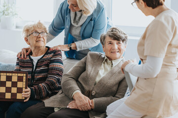 Older ladies sit on a couch and talk to a nurse at a local nursing home