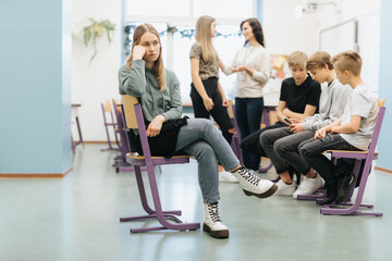 Pretty thoughtful teenage girl sits on the side of a group during extracurricular activities at...