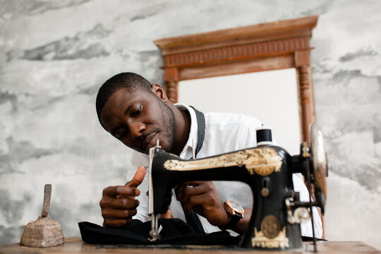 Portrait of a black man seamstress sewing himself a black suit to demonstrate at the exhibition of his work in the studio