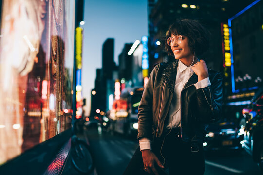 Smiling young woman in gorgeous apparel listening favorite song in earphones walking on night urban city street, happy hipster girl 20s enjoying music spending evening in illuminated Manhattan